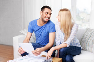 couple with paper bills and calculator at home