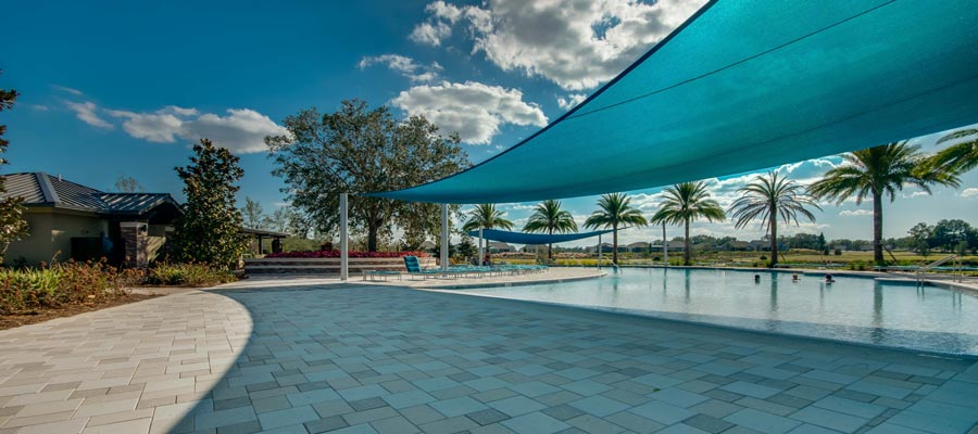 A stylish, pristine pool with awning sun shield providing shaded areas.