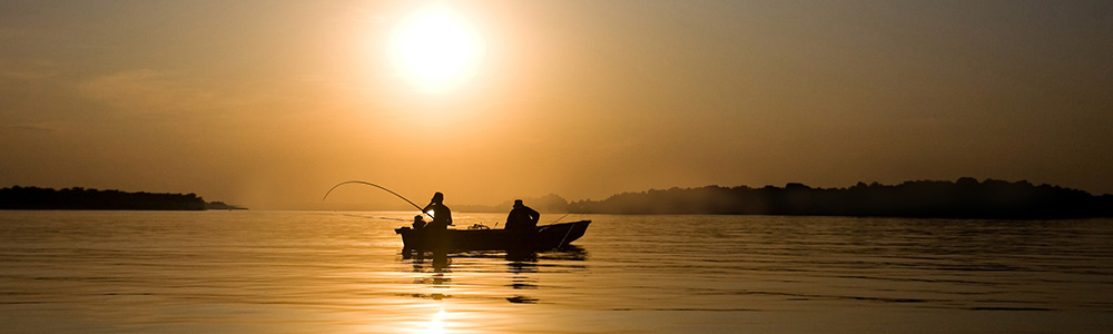 Fishermen in a boat on a lake at sunrise.
