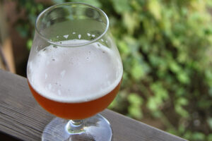 A glass of beer on a wooden deck railing.