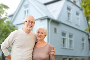 happy senior couple hugging over house background