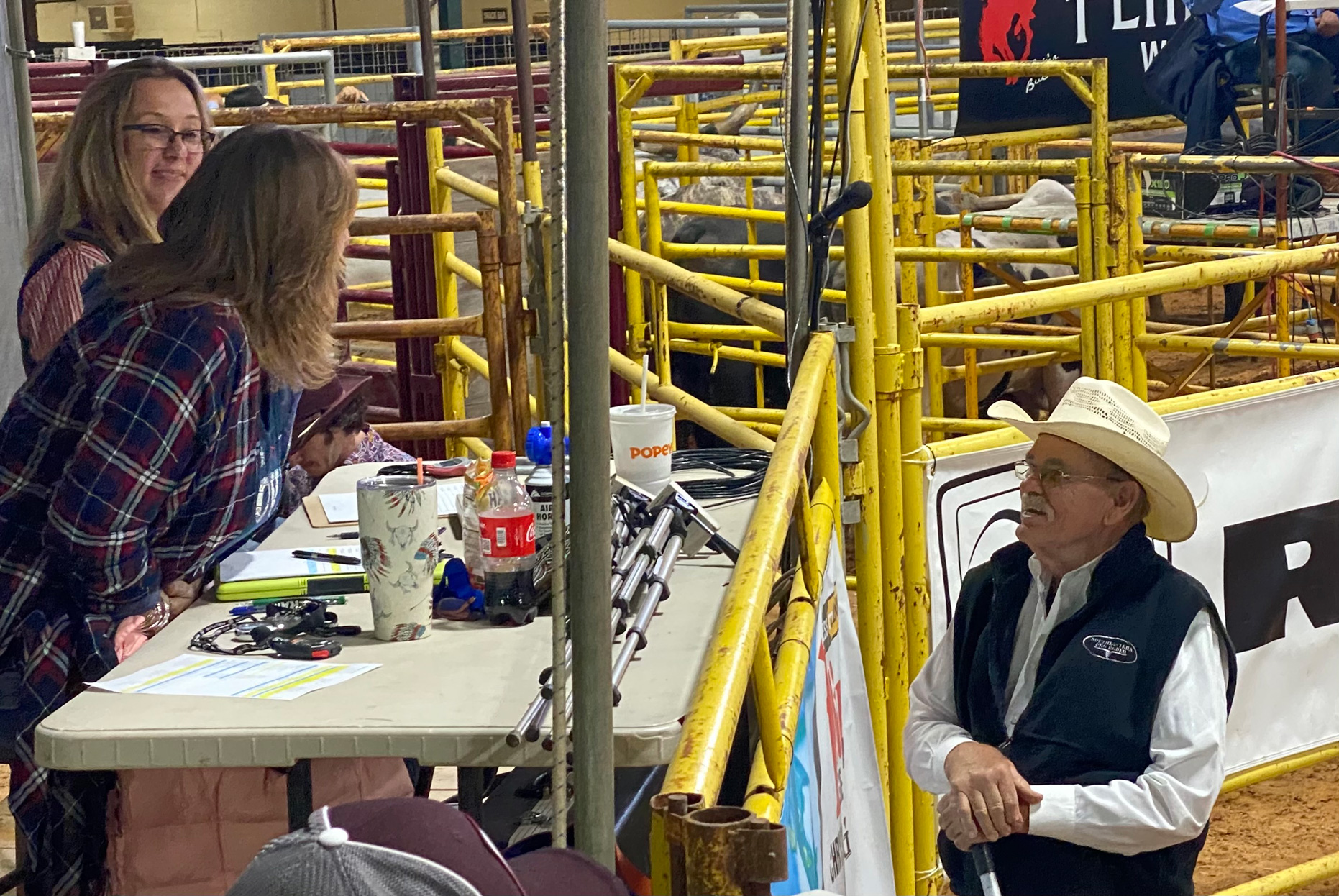 Ruben Lamb speaks to two audience members at the Southeastern Pro Rodeo in 2021.
