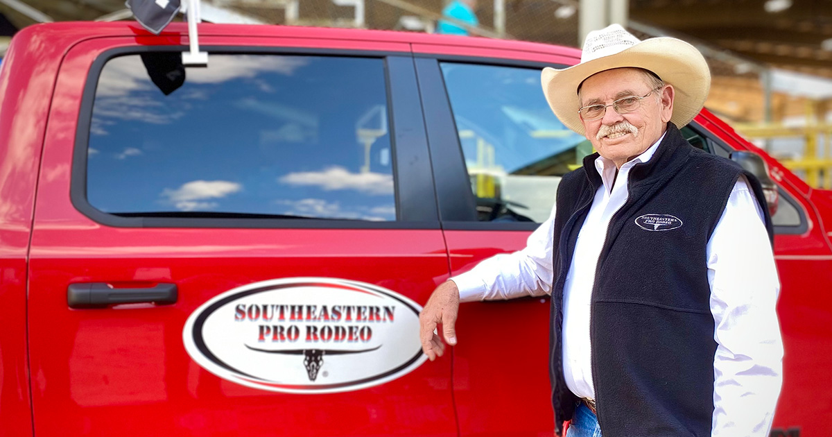 Ruben Lamb poses in front of his pick up truck, which has the Southeastern Pro Rodeo logo on the side.