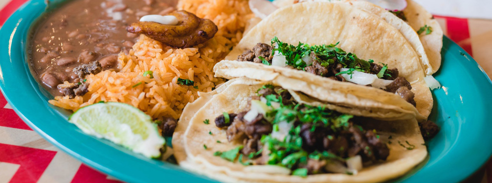A heaping helping of tacos with all the sides.