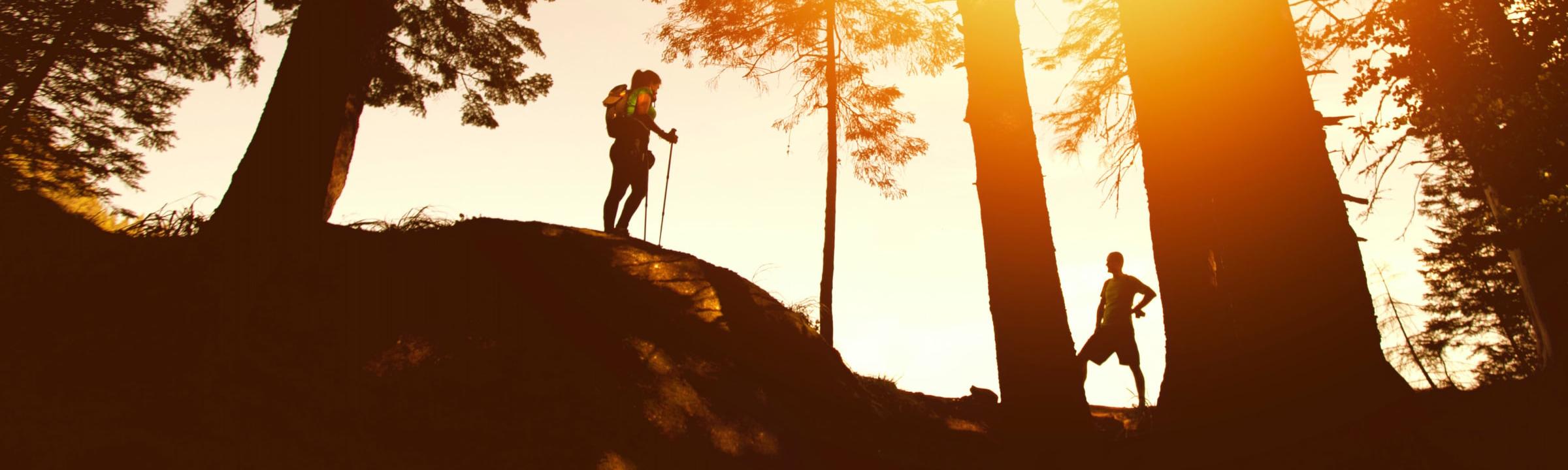 A couple hiking on a ridge at sunset.