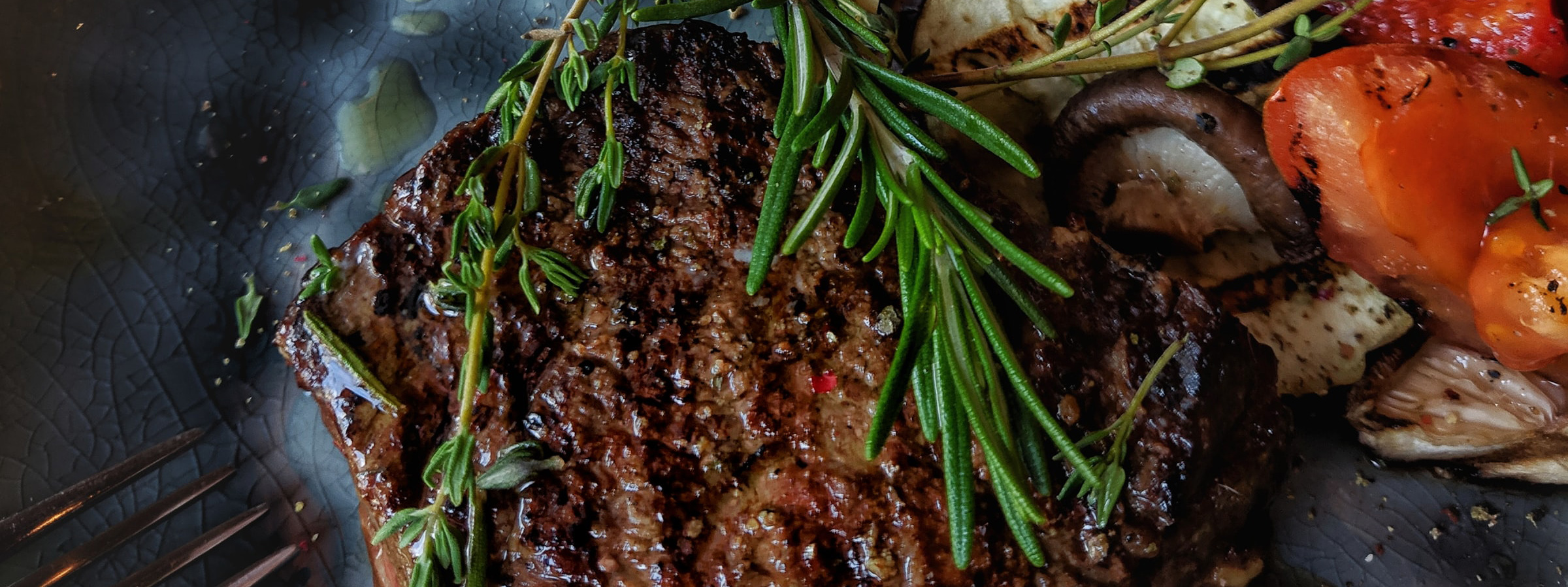 Steak with rosemary and sauteed vegetables.