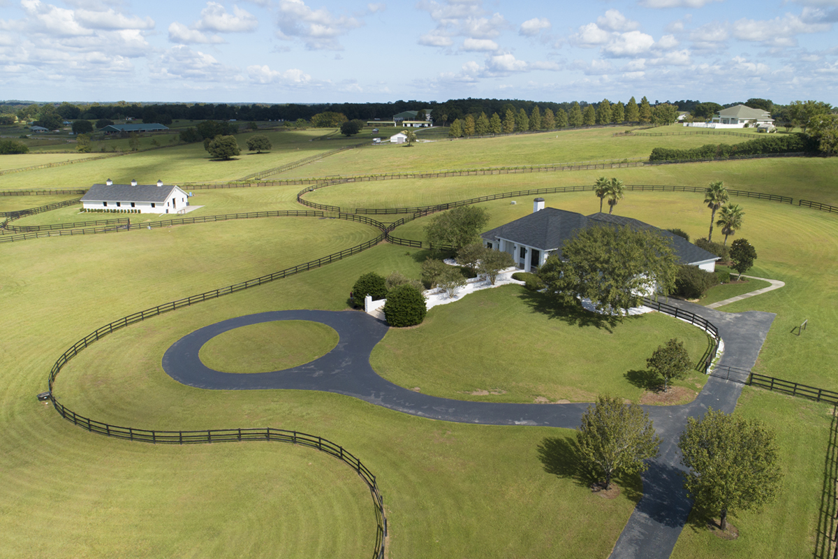 A aerial view of a stunning horse farm resting on a hill.