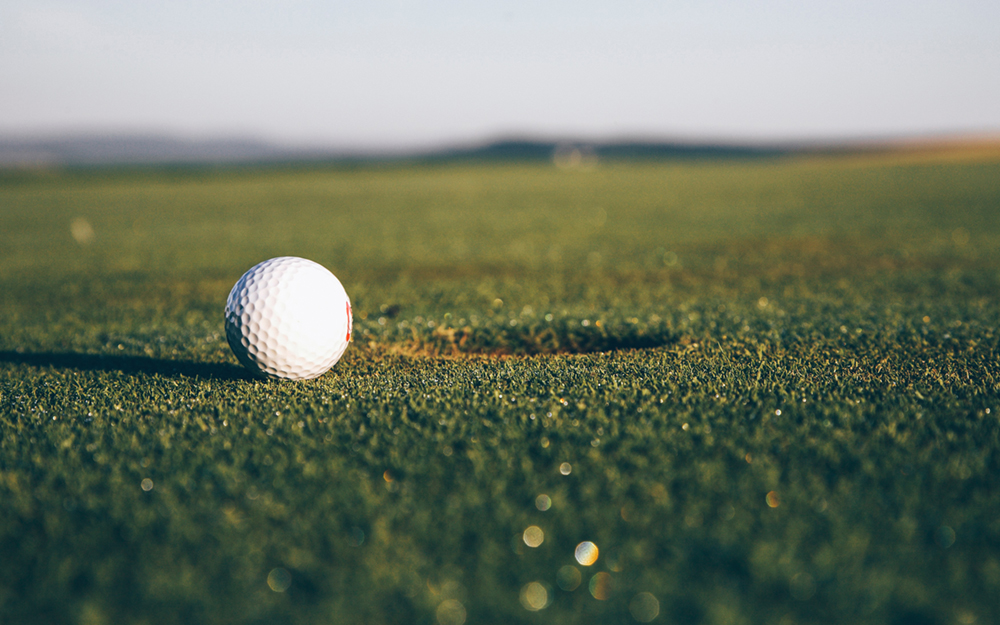 A golf ball about to go into the hole.