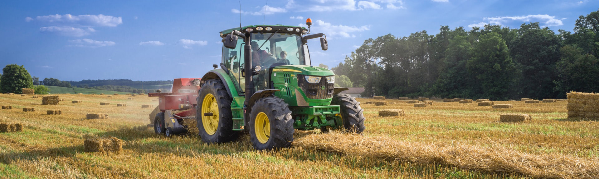 A tractor working on bales of hay.