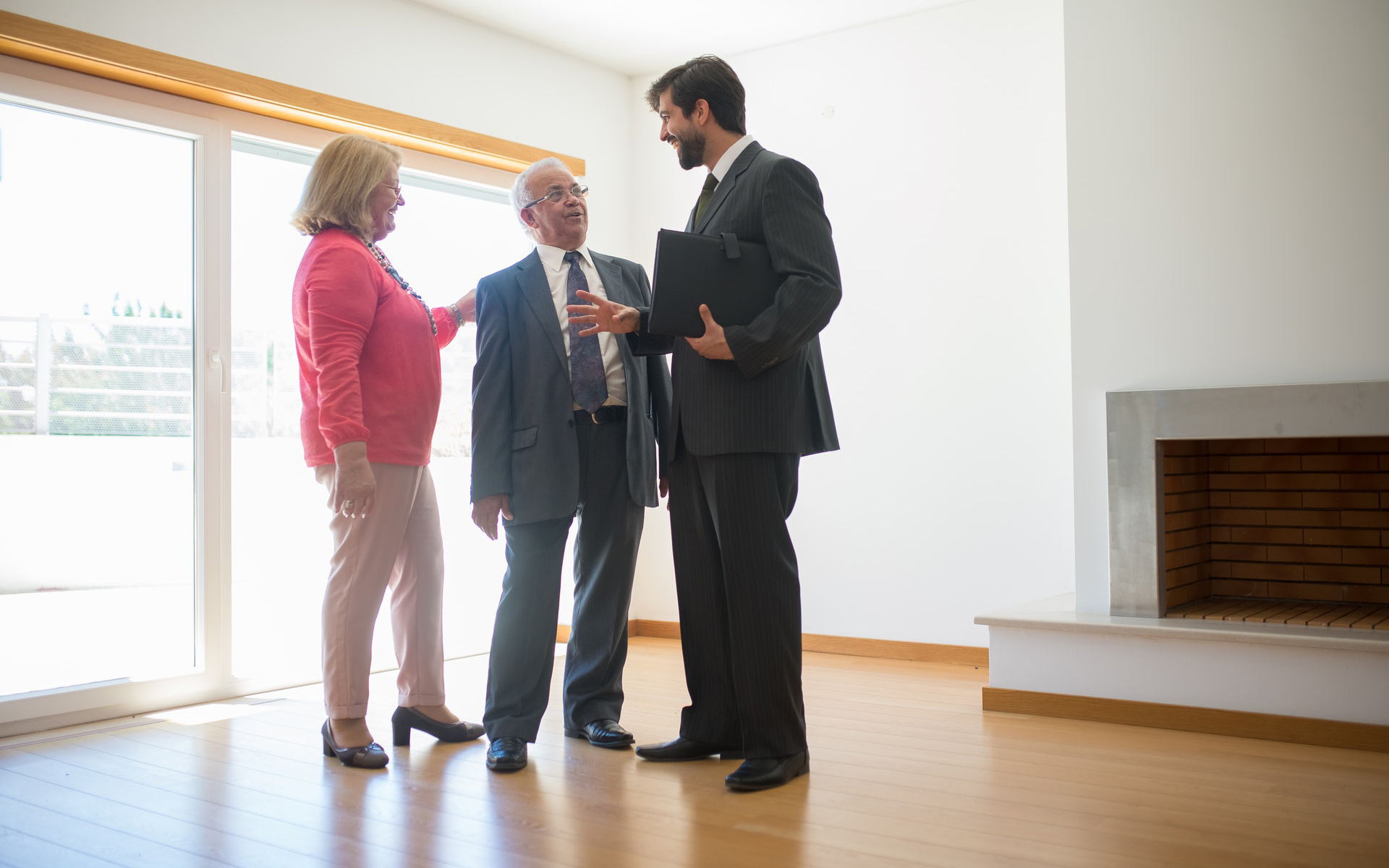 A senior couple being shown a home by a REALTOR®