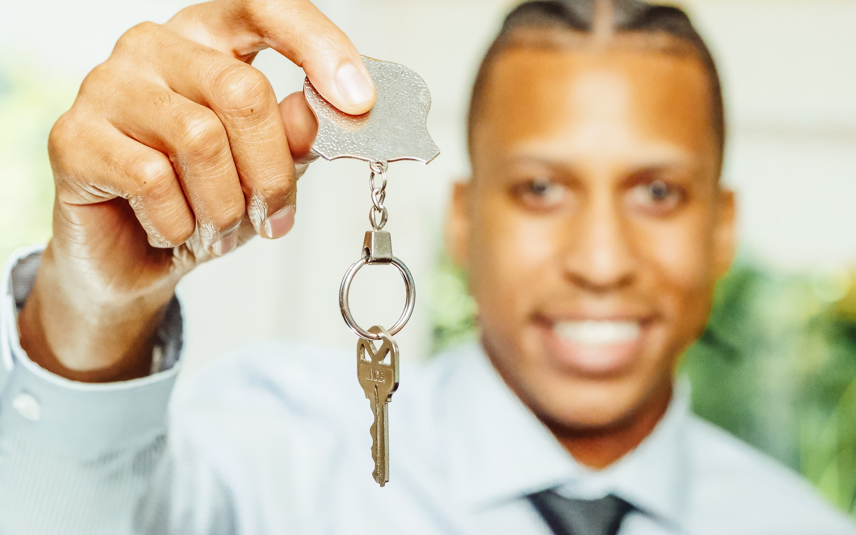 A real estate agent holding the keys to a home.