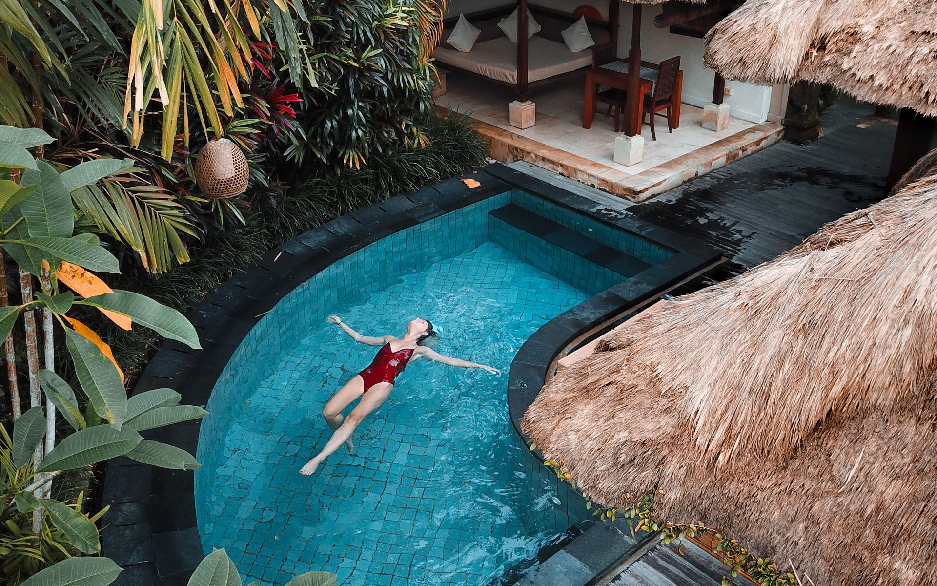 A woman swimming in a luxurious tropical pool.