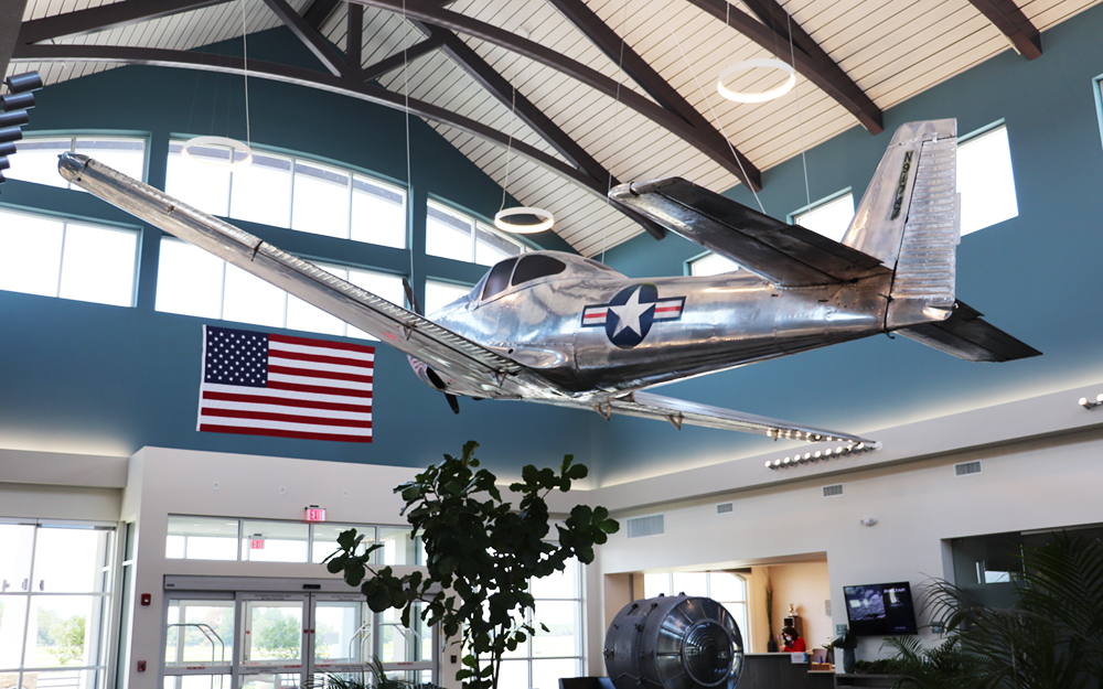 Soaring over the room, as if in mid-flight, is an almost pristine 1947 North American Navion suspended from the ceiling directly above a huge, original signal beacon from when the airport was first built.